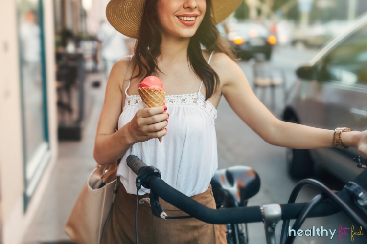 Woman eating ice cream while holding bike